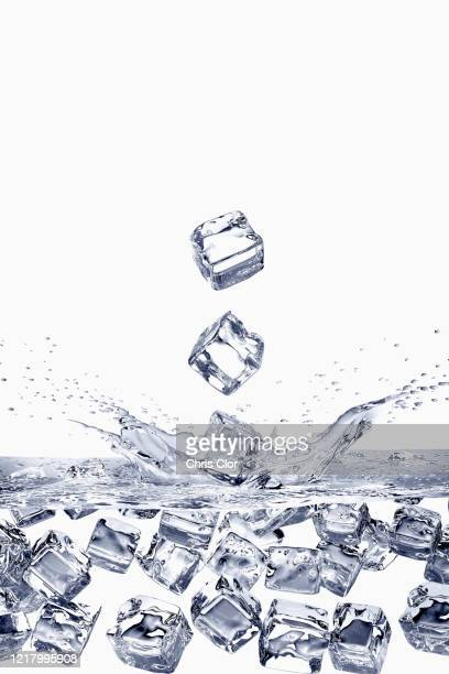 ice cubes falling into water - ice cube stock pictures, royalty-free photos & images