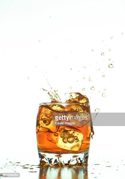 ice cubes splashing in whiskey over white background - scotch whiskey stock pictures, royalty-free photos & images