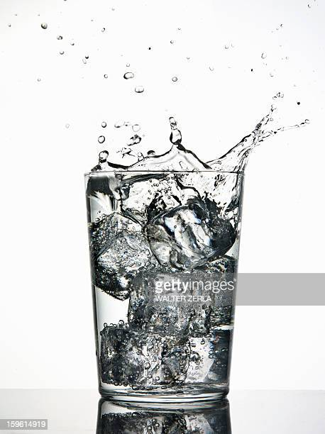 Ice cubes splashing into fizzy drink