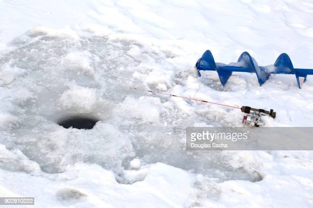 Ice cutting Auger and Fishing rod on the ice