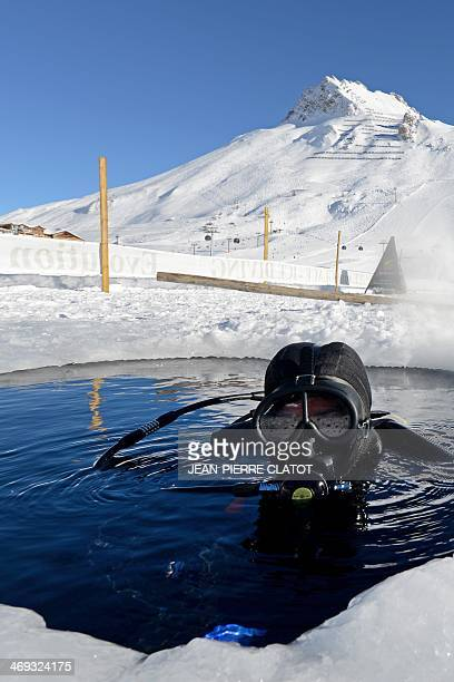 Ice diving instructor Benjamin Roch readies his gear before going under the frozen Lake of Tignes100 meters high in the French Alps on February 11...