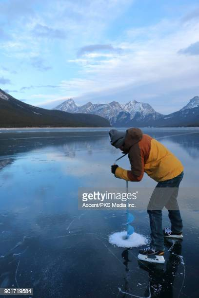 Ice fisher bores whole into lake ice in mountains