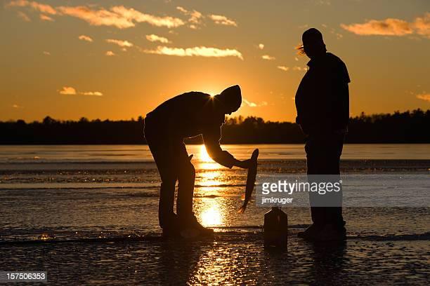 Ice fisherman catching fish on frozen lake at sunset.