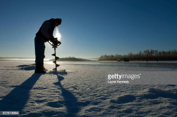 Ice fisherman drilling hole in ice on the Missouri River