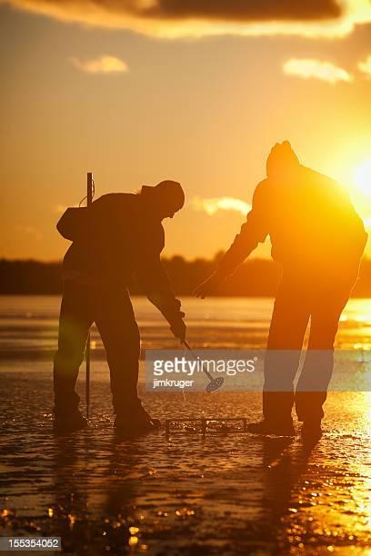 Ice fisherman on frozen lake at sunset.