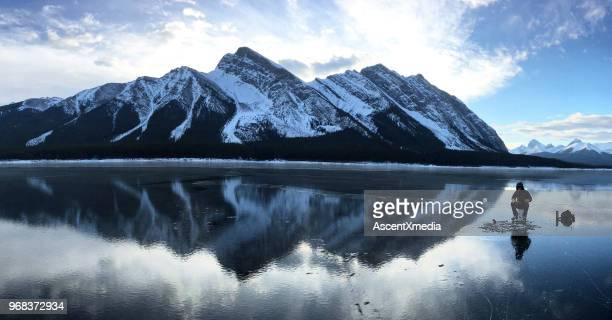 ice fishermen on frozen lake in the mountains - ice fishing stock pictures, royalty-free photos & images