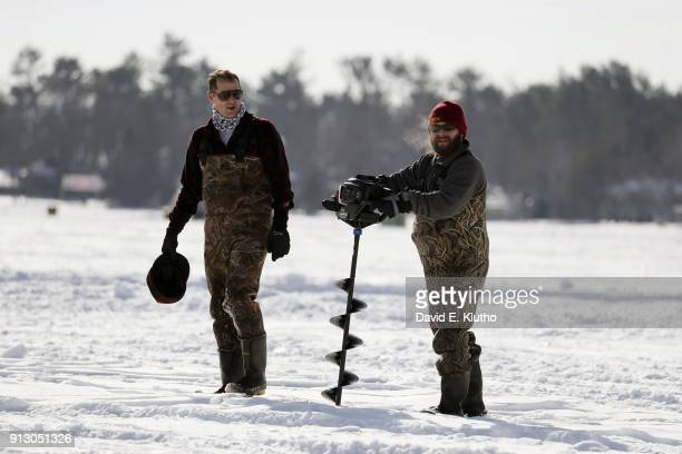 Brainerd Jaycees Ice Fishing Extravaganza View of contestants drilling hole in ice with auger during event on Brainerd Lakes Contestants came from 38...
