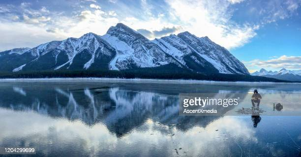 ice fishing on frozen mountain lake - ice fishing stock pictures, royalty-free photos & images