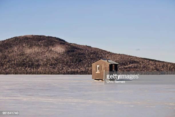 Ice fishing shack on frozen lake near Jackman, Maine, USA