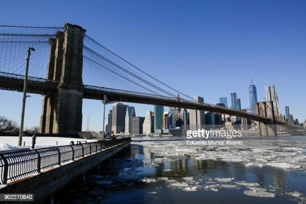 Ice floats along the East River as the skyline of New York City Brooklyn Bridge and One World Trade Center are seen during freezing temperatures on...