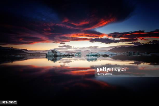 ice floe and dramatic sunset reflecting in jokulsarlon lake, iceland - banquisa flotante fotografías e imágenes de stock