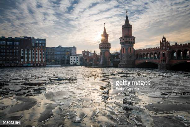 Ice floes are pictured on the river Spree during the sunset behind the bridge 'Oberbaumbruecke' on March 05 2018 in Berlin Germany