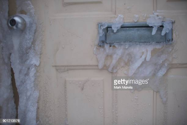 Ice forms on the front door of a residence on January 4 2018 in Atlantic City New Jersey A 'bomb cycle' winter storm has caused every East Coast...