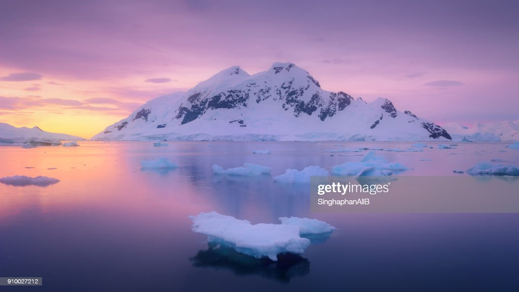 ice glacier floating in the lagoon with the snowcapped mountain sunset at antarctica : Stock Photo