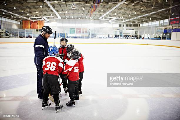 ice hockey coach encouraging young team - hockey player stock pictures, royalty-free photos & images