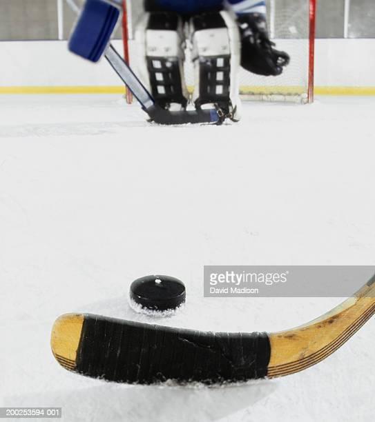 Ice hockey goalie protecting net (focus on hockey stick and puck)
