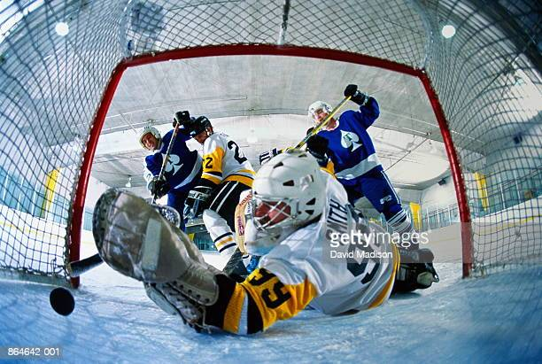 ice hockey, goalie reaching for puck rolling into goal (wide angle) - difensore hockey su ghiaccio foto e immagini stock