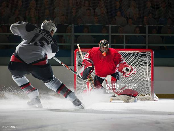 ice hockey goalkeeper blocking a shot - shooting at goal photos et images de collection