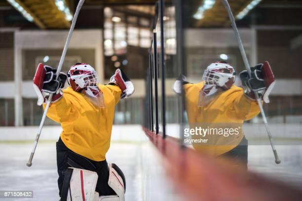 Gardien de but de hockey sur glace célèbre jeu à succès avec les bras levés.