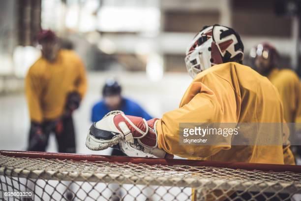 ice hockey keeper verdedigen zijn doel op een wedstrijd. - doelman ijshockeyer stockfoto's en -beelden