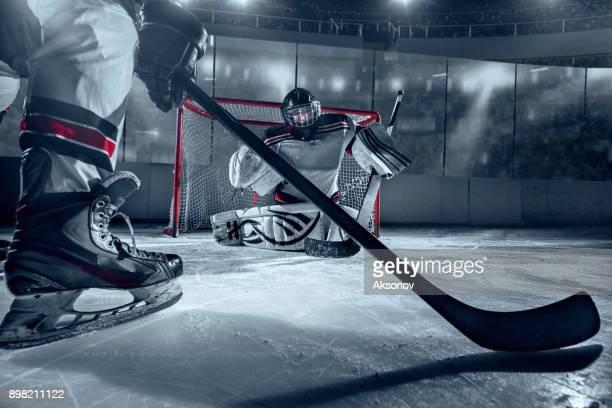 ijshockeyspeler en doelman op grote professionele ijs arena - ijshockeytenue stockfoto's en -beelden