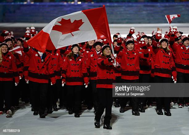 Ice hockey player Hayley Wickenheiser of the Canada Olympic team carries her country's flag during the Opening Ceremony of the Sochi 2014 Winter...