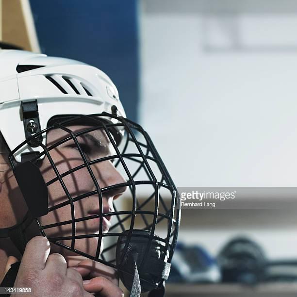 Ice hockey player putting on helmet, close up