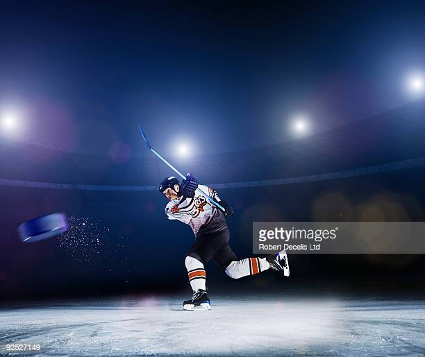 Ice hockey player shooting puck.