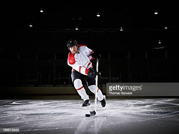 Ice hockey player skating down ice with puck