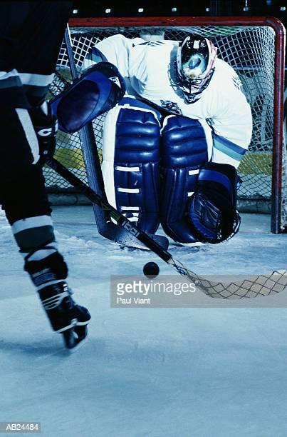 Ice Hockey player with opposing goal tender