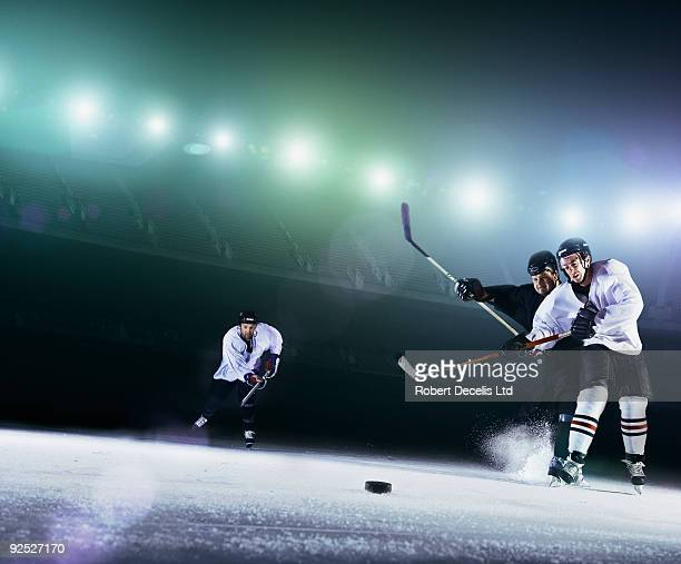 Ice hockey players challenging for puck