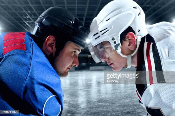Ice hockey players from opposing teams face to face