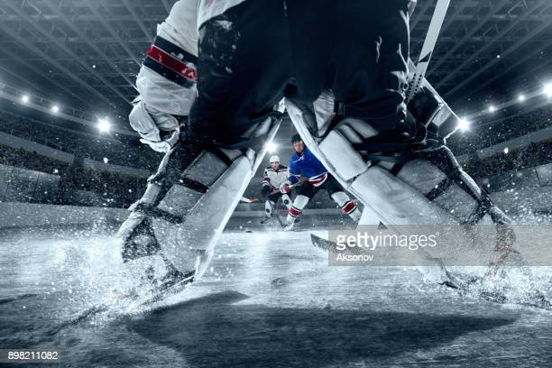 ice hockey players on big professional ice arena. view from the hockey gate - hockey stock pictures, royalty-free photos & images