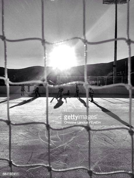 ice hockey players on rink against sky seen from net - ice hockey rink stock pictures, royalty-free photos & images