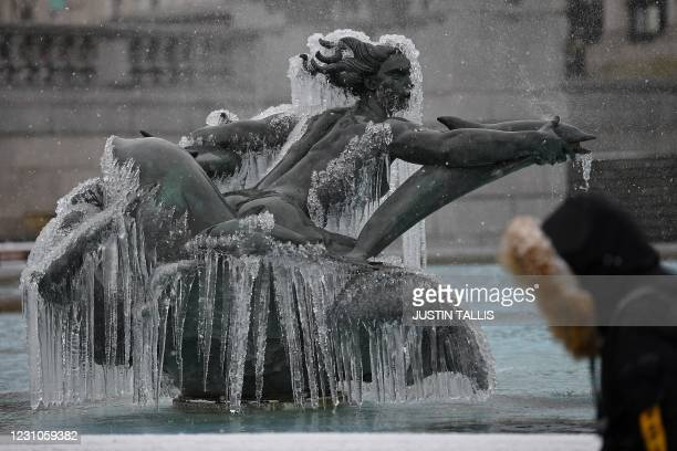 Ice is pictured on a mermaid statue in one of the fountains in Trafalgar Square in London on February 9, 2021. - Cold weather swept across northern...