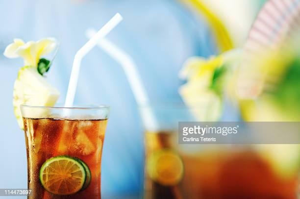 Ice lemon tea with pineapple and orchid garnish