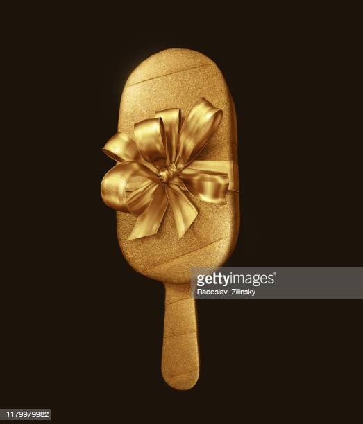 ice lolly covered with golden wrapping - shiny stock pictures, royalty-free photos & images