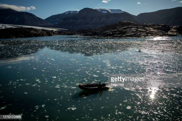 Ice melts near Nordenskjodbreen glacier as man past by with a boat on August 25, 2020 on the Norwegian Arctic Svalbard archipelago, Norway....