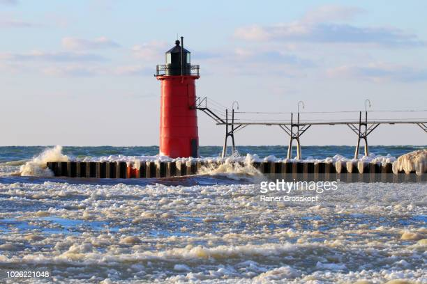ice on frozen pier and lighthouse in winter - rainer grosskopf foto e immagini stock