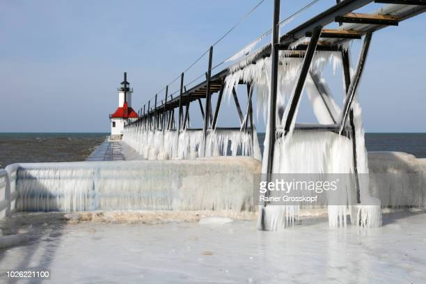 ice on frozen pier and lighthouse in winter - rainer grosskopf stock pictures, royalty-free photos & images