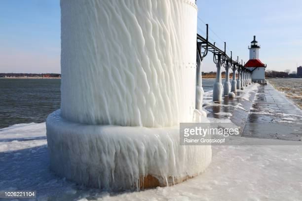 Ice on frozen pier and Lighthouse in winter