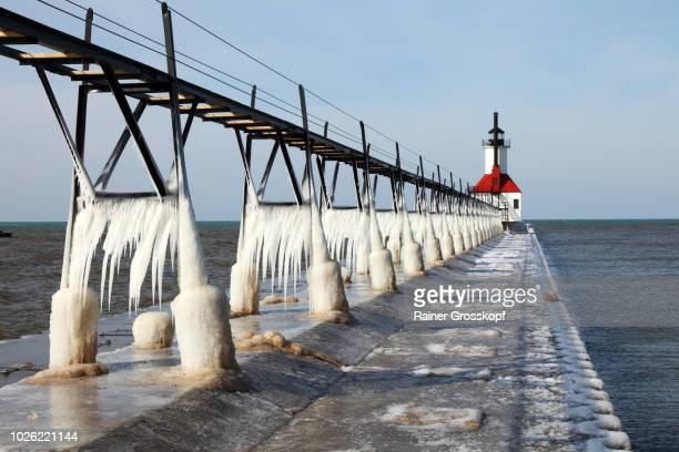 ice on frozen pier and lighthouse in winter - rainer grosskopf stock-fotos und bilder