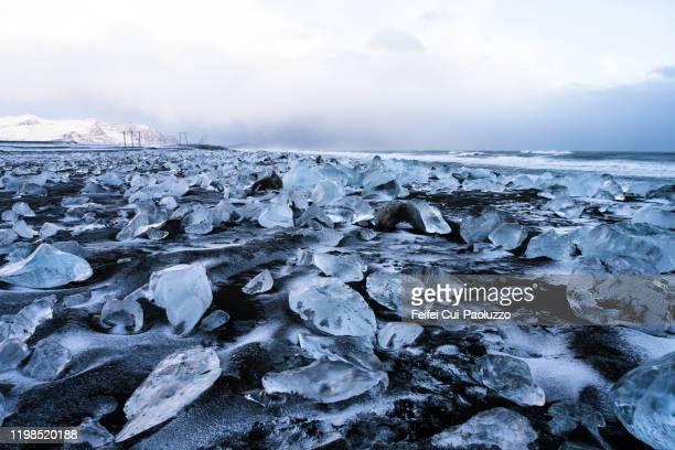 ice on the black sand beach of jökulsárlón, east iceland - 氷河湖 ストックフォトと画像