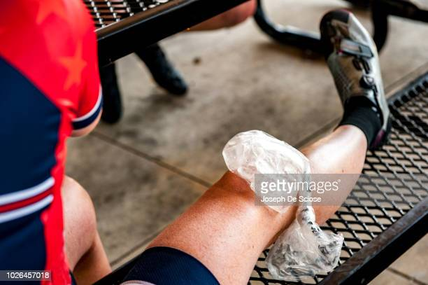 ice pack on woman's knee - human knee stock pictures, royalty-free photos & images