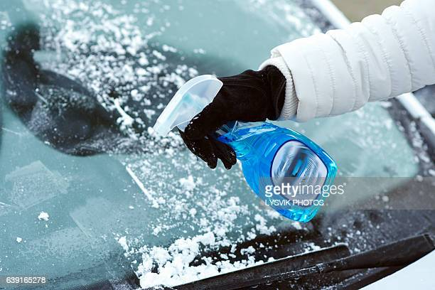 ice scraping en defrost spray on car windscreen - scraping stock photos and pictures