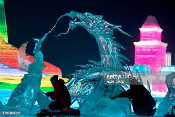 Ice sculptors give finishing touches on an ice sculpture ahead of the opening of the Harbin International Ice and Snow Festival in Harbin in China's...