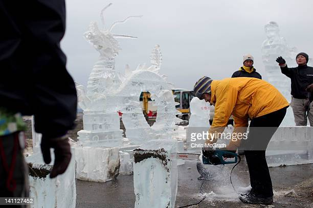 Ice sculptors work to complete their pieces for the anniversary of last year's deadly earthquake and tsunami in the early morning hours of March 11...