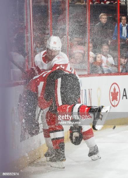 Ice shavings fly as Jack Rodewald of the Ottawa Senators and Xavier Ouellet of the Detroit Red Wings collide in the end boards at Canadian Tire...