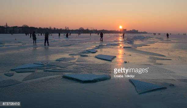 Ice sheets and skaters at sunset