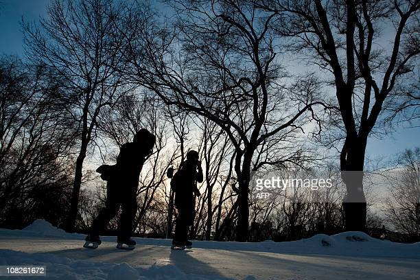 Ice skaters are silhouetted during La fête des Neiges Montréal's great winter festival where families are invited to play outdoors and enjoy an array...